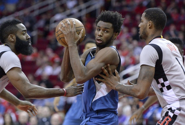 Andrew Wiggins drove between Houston's James Harden, left, and Trevor Ariza in the first half Saturday in Houston.