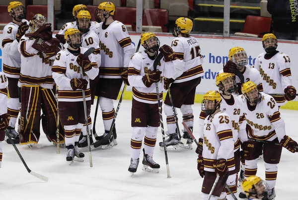 The Minnesota team stands on the ice after a 4-3 loss to Penn State in two overtimes in a semifinal of the Big Ten college hockey tournament, Friday,