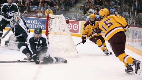Michigan State's Rhett Holland slid over to protect the open side of the net on a scoring bid by the Gophers' Rem Pitlick (15) in the first period