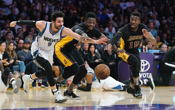 Minnesota Timberwolves guard Ricky Rubio, left, of Spain, scrambles for a loose ball along with Los Angeles Lakers forward Julius Randle, center, and