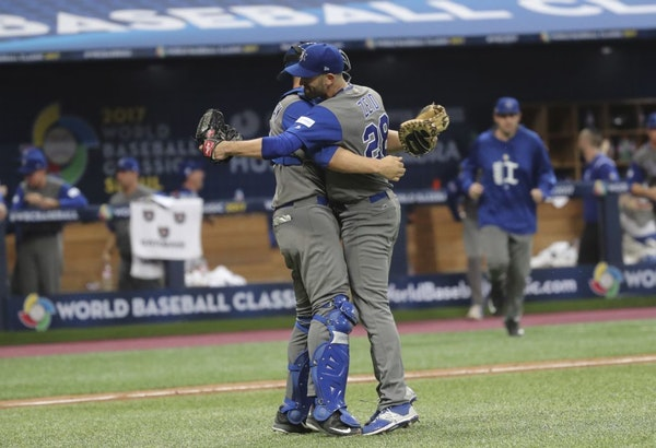 Israel's pitcher Josh Zeid, right, celebrates his team's victory with catcher Ryan Lavarnway against South Korea after the first round game of the Wor