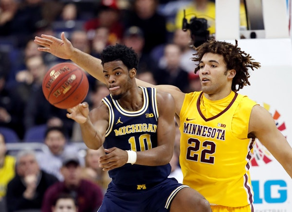 Michigan guard Derrick Walton Jr. (10) passes the ball as he is guarded by Minnesota center Reggie Lynch (22) during the first half of an NCAA college