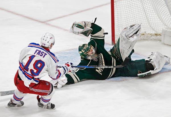 A falling Minnesota Wild goalie Devan Dubnyk, right, blocks a shot by New York Rangers' Jesper Fast during the first period of an NHL hockey game Satu