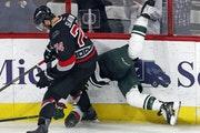 The Carolina Hurricanes' Jaccob Slavin (74) upends the Minnesota Wild's Jason Pominville (29) as he slams him into the boards during the third period