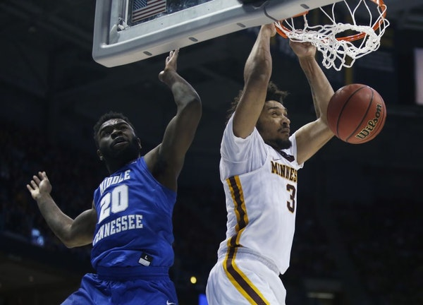 Minnesota's Jordan Murphy dunks past Middle Tennessee State's Giddy Potts during the second half of an NCAA college basketball tournament first round