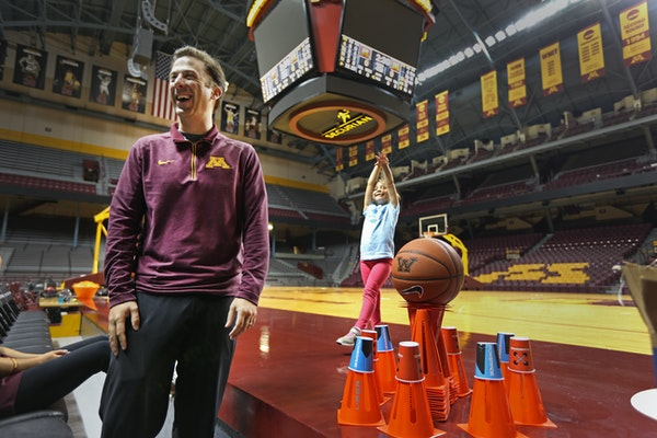 Richard Pitino with two of his children at Williams Arena earlier this season. Pitino said he no longer gets asked on the ride to school if Daddy's te