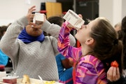 Sioux Trail Elementary third-graders, Salma Omar, left, and Marriana Ristamaki-McKee tried to drink their milk.