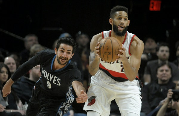 Minnesota Timberwolves guard Ricky Rubio reaches in to try and steal the ball from Portland Trail Blazers guard Allen Crabbe during the first half of