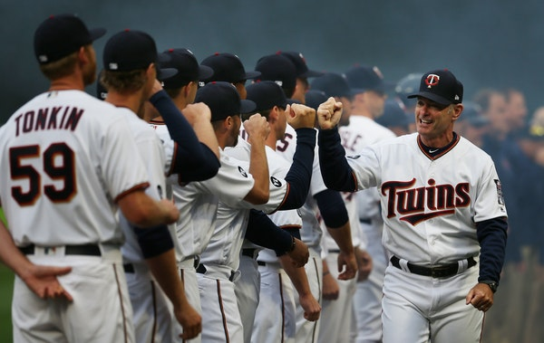 Twins manger Paul Molitor fist bumped members of his team at Target Field on Opening Day.