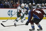 Minnesota Wild center Eric Staal, center, takes a shot as he skates between Colorado Avalanche defensemen Tyson Barrie, front, and Anton Lindholm, of