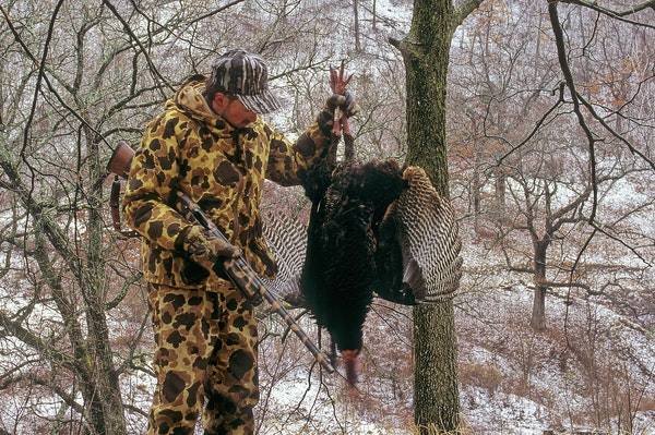 Marchel admires a big gobbler taken in blizzard-like conditions.