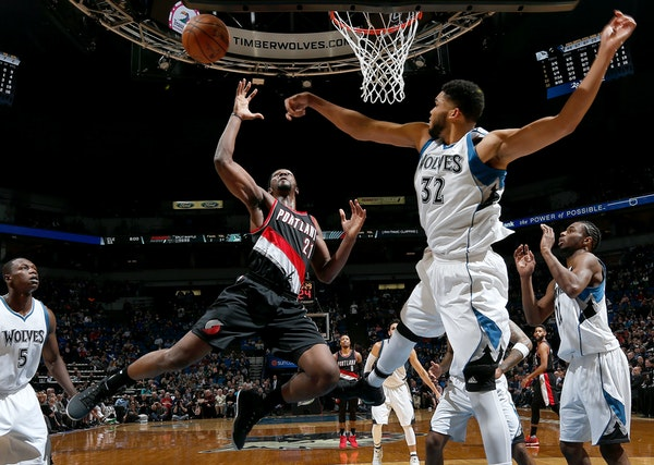 Minnesota Timberwolves' Karl-Anthony Towns (32) defends a shot by Portland Trail Blazers' Noah Vonleh (21) in the third quarter on Monday, April 3, 20