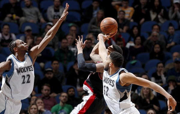 Andrew Wiggins (22) and Karl-Anthony Towns attempted to block a shot by Damian Lillard (0) in the fourth quarter.