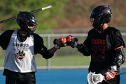 Twin brothers Dayton, left, and Dante Buck fist-bumped before a lacrosse game against Eastview High School Thursday.