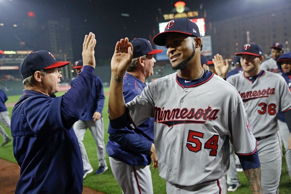 Minnesota Twins starting pitcher Ervin Santana (54) celebrates with coaches and teammates after closing out a baseball game against the Baltimore Orio