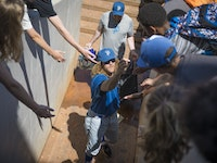 St. Paul Saints pitcher Mark Hamburger handed out gum to kids after Education Day at a St. Paul Saints exhibition game in St. Paul, Minn., on Tuesday,