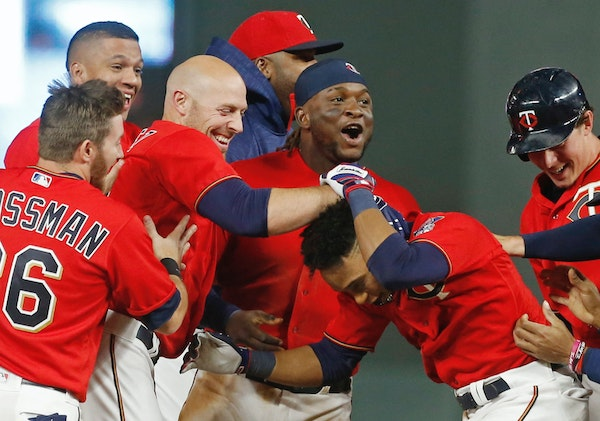 Minnesota Twins' Jorge Polanco, right, is swarmed by teammates after his walk-off sacrifice fly in the 10th inning of a baseball game against the Kans