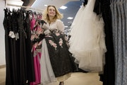 Ali-Jae Nicolai, 17, a junior at New Prague High School, carries a selection of dresses while shopping for prom dresses at Macy's at the Mall of Ameri