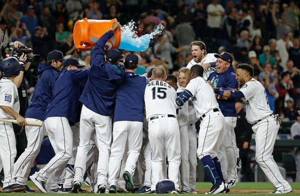 Seattle Mariners players surround Mike Zunino and tip a giant container of sports drink over the crowd after his two-run home run in the ninth inning