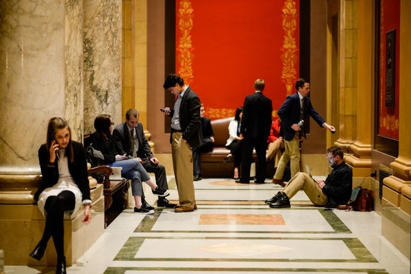 Staffers and lobbyists waited in the lobby outside the House chamber Tuesday night during a recess in the Minnesota Legislature's special session.