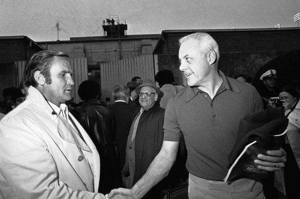Miami coach Don Shula, the winner, is rather grim while the loser, Minnesota coach Bud Grant, has a smile as they meet in the Rice Stadium tunnel foll