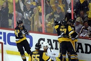Pittsburgh Penguins' Brian Dumoulin (8) and Carter Rowney (37) celebrate with Nick Bonino after Bonino's goal against the Nashville Predators during t