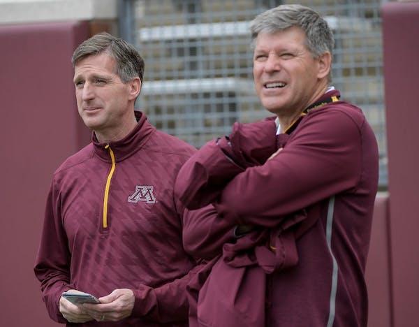 University of Minnesota Athletic Director Mark Coyle joked with athletics fundraiser Randy Handel on the sidelines of Minnesota football's spring game