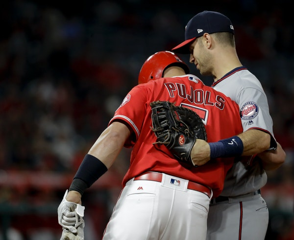 Los Angeles Angels' Albert Pujols, left, gets a hug from Minnesota Twins first baseman Joe Mauer after a base hit during the fourth inning of a baseba