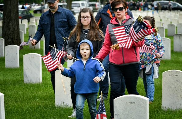 Max Payne, 5, found a grave marker where he wanted to place his flag. He came to Fort Snelling Monday with his parents Dave and Sonya and siblings Chl