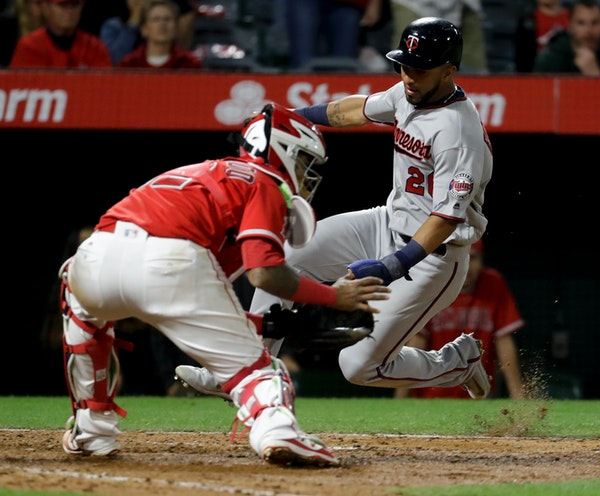 Minnesota Twins' Eddie Rosario, right, scores past Los Angeles Angels catcher Martin Maldonado on a hit by Jason Castro during the ninth inning of a b