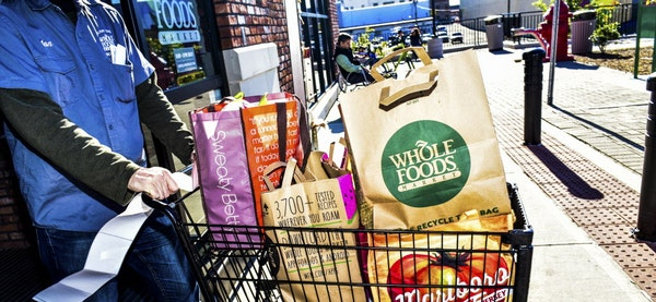 FILE ó A Whole Foods employee pushes a laden cart out of the store, in New York, Oct. 30, 2015. Amazonís $13.4 billion purchase of Whole Foods is a