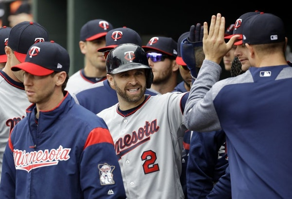 Brian Dozier high-fives teammates in the dugout after scoring on an RBI double by Kennys Vargas in the first inning against the Baltimore Orioles on W