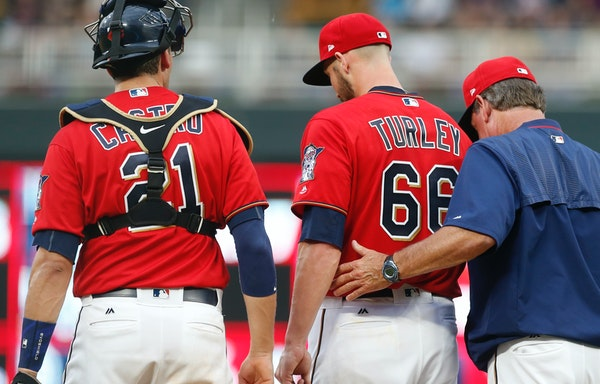 Minnesota Twins pitcher Nink Turley, center, gets support on the mound by pitching coach Neil Allen, right, in the third inning of a baseball game aga