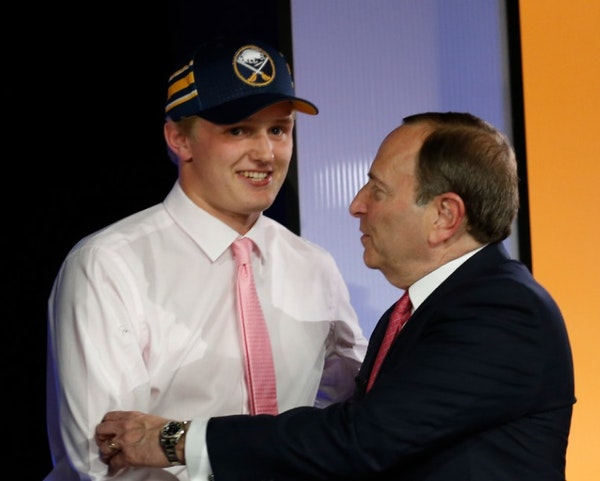 Casey Mittelstadt, left, shakes hands with NHL Commissioner Gary Bettman after being selected by the Buffalo Sabres in the first round of the NHL hock