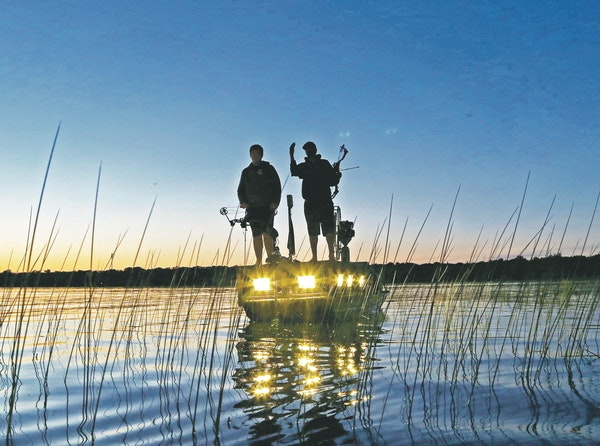 """Men of the night: Bowfishermen hunt carp and other """"rough'' fish long after the sun goes down, using their boat's bright lights to illuminate"""