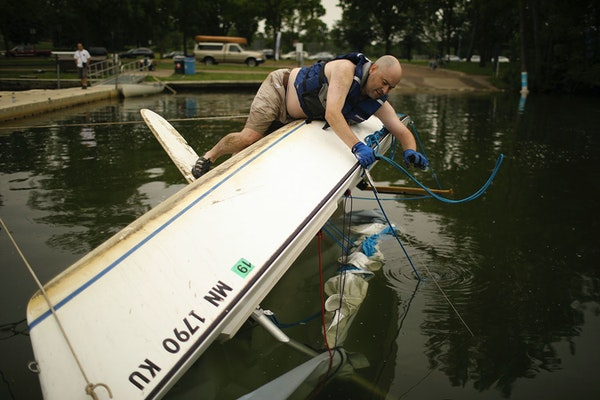 Martin Conroy got a rope squared away as he waited for some help from others as they attempted to right his overturned sailboat on Lake Nokomis Sunday