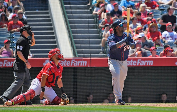 Minnesota Twins' Miguel Sano, right, hits a two-run home run as Los Angeles Angels catcher Juan Graterol, center, watches along with home plate umpire