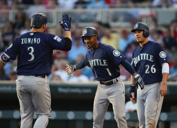 Seattle's Jarrod Dyson (1) and Danny Valencia (26) greeted teammate Mike Zunino at home after his three run homer in the third inning put the Mariners