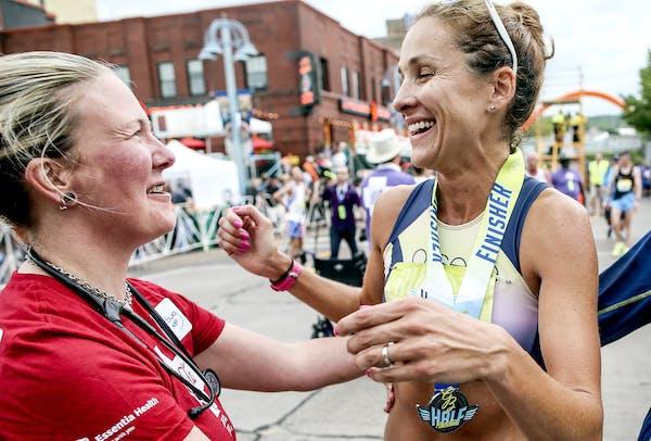 Jitterbug Pierce congratulated Kara Goucher, right, at the finish line of the Garry Bjorklund Half Marathon on Saturday morning in Duluth.