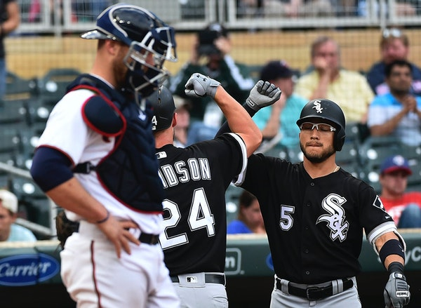 Chicago White Sox's Matt Davidson is congratulated by Yolmer Sanchez after hitting a solo home run against the Minnesota Twins during the ninth inning