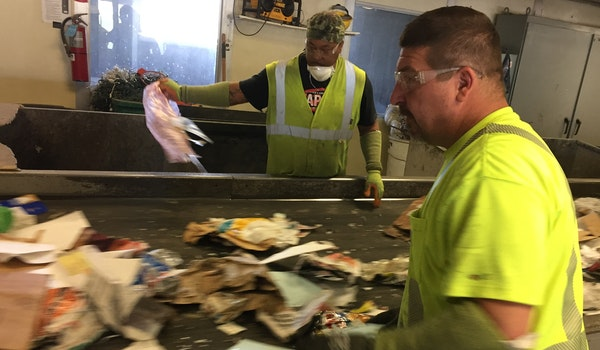 Workers at Dem-Con's recycling center in Shakopee raced to remove non-recyclable items before they enter the sorting machines.
