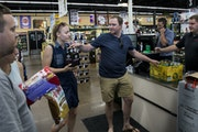 Travis Heins hands over hard cider to his wife, Kelsey Heins, at Chicone's Liquor Mart in Hudson, Wis., on Monday, a day after Sunday liquor sales b