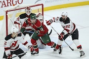 Minnesota Wild center Mikael Granlund (64) is shoved by New Jersey Devils defenseman Kyle Quincey (22) as he screens goalie Cory Schneider just as an