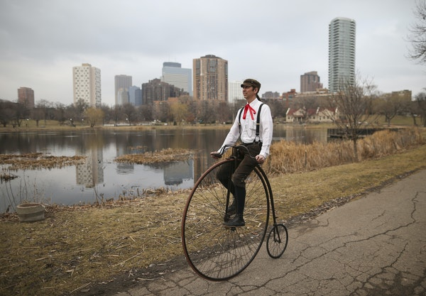Bicycle enthusiast Juston Anderson rides an 1890 Victor high wheeler bicycle in Loring Park.