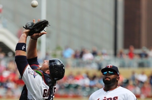 Twins catcher Chris Gimenez caught a popup by the Orioles' Mark Trumbo as third baseman Miguel Sano looked on Sunday.