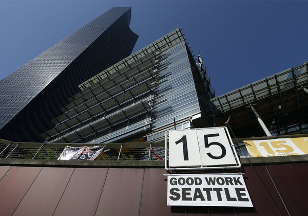 """A sign reading """"15 Good Work Seattle"""" was displayed below Seattle City Hall, right, and the Columbia Center building, left, after the Seattle City"""