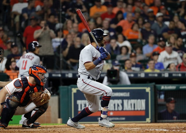 Minnesota Twins' Eddie Rosario, right, watches his single along with Houston Astros catcher Evan Gattis during the eighth inning of a baseball game Sa