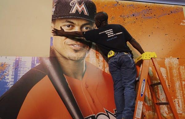 Francois Diesiul hanged a poster bearing Miami star Giancarlo Stanton at the Miami Beach Convention Center. in Miami Beach, Fla., where baseball's A