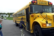 Students boarded a traditional bus on their way to school. The electric bus' exterior will look the same as this one.