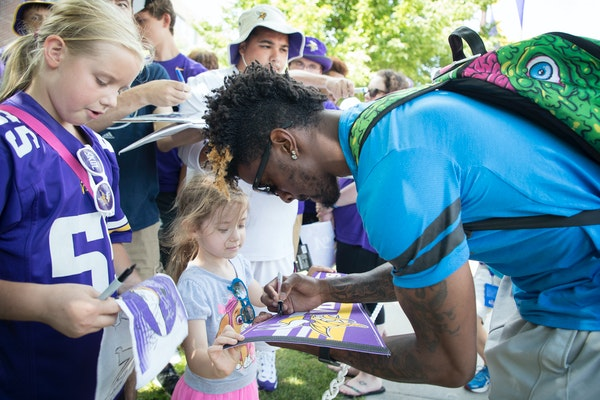Rodney Adams autographed a pennant for Tylar Amberg, 4, as he arrived at Vikings training camp at Mankato.